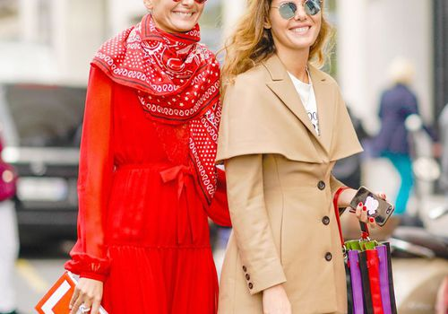 two woman walking down the street in fashionable clothing