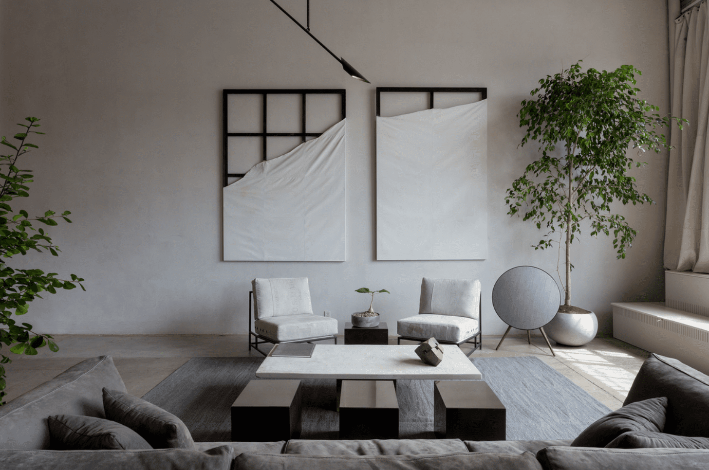 A living room with large bare walls decorated with metal frames draped with fabric