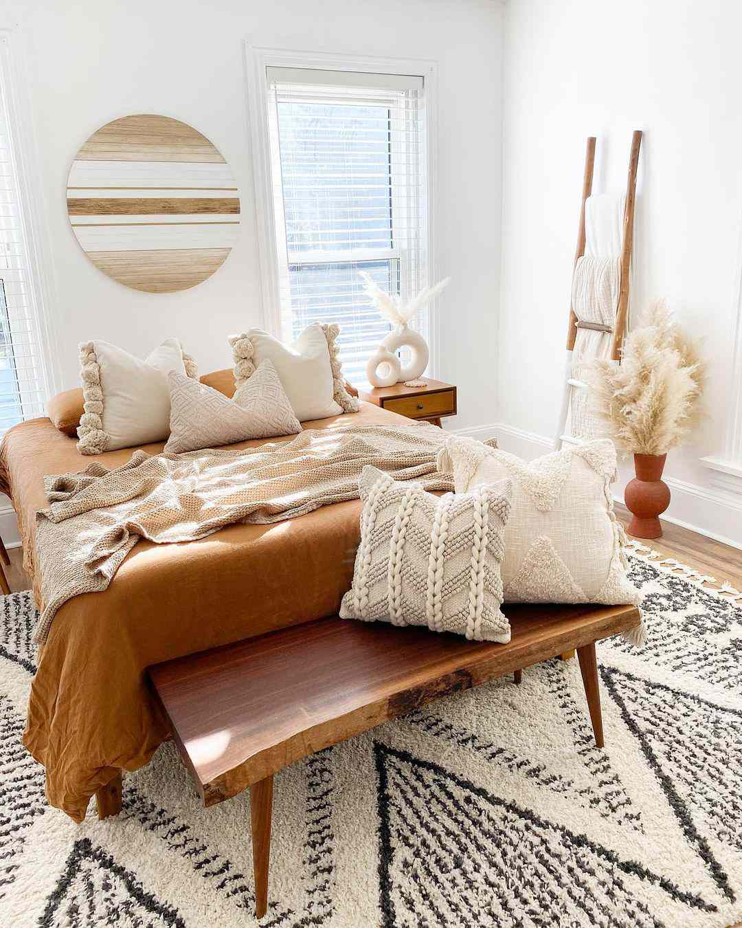 Boho inspired bedroom with textured neutral pillows and blankets.