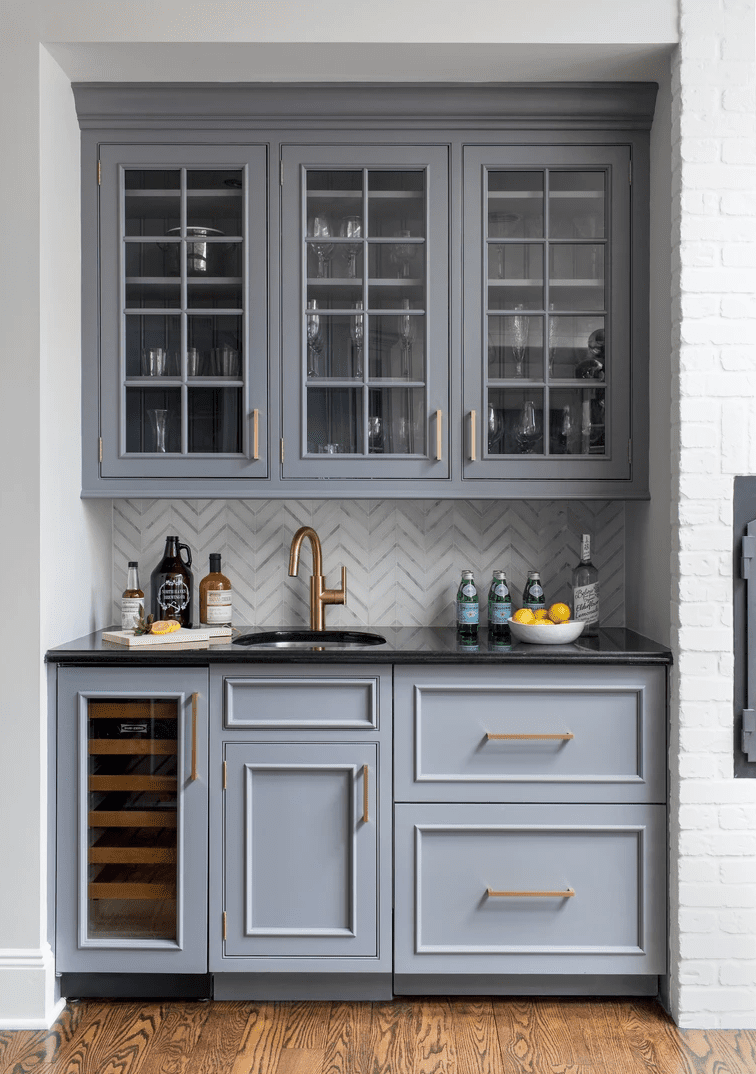 A wet bar with gray cabinets
