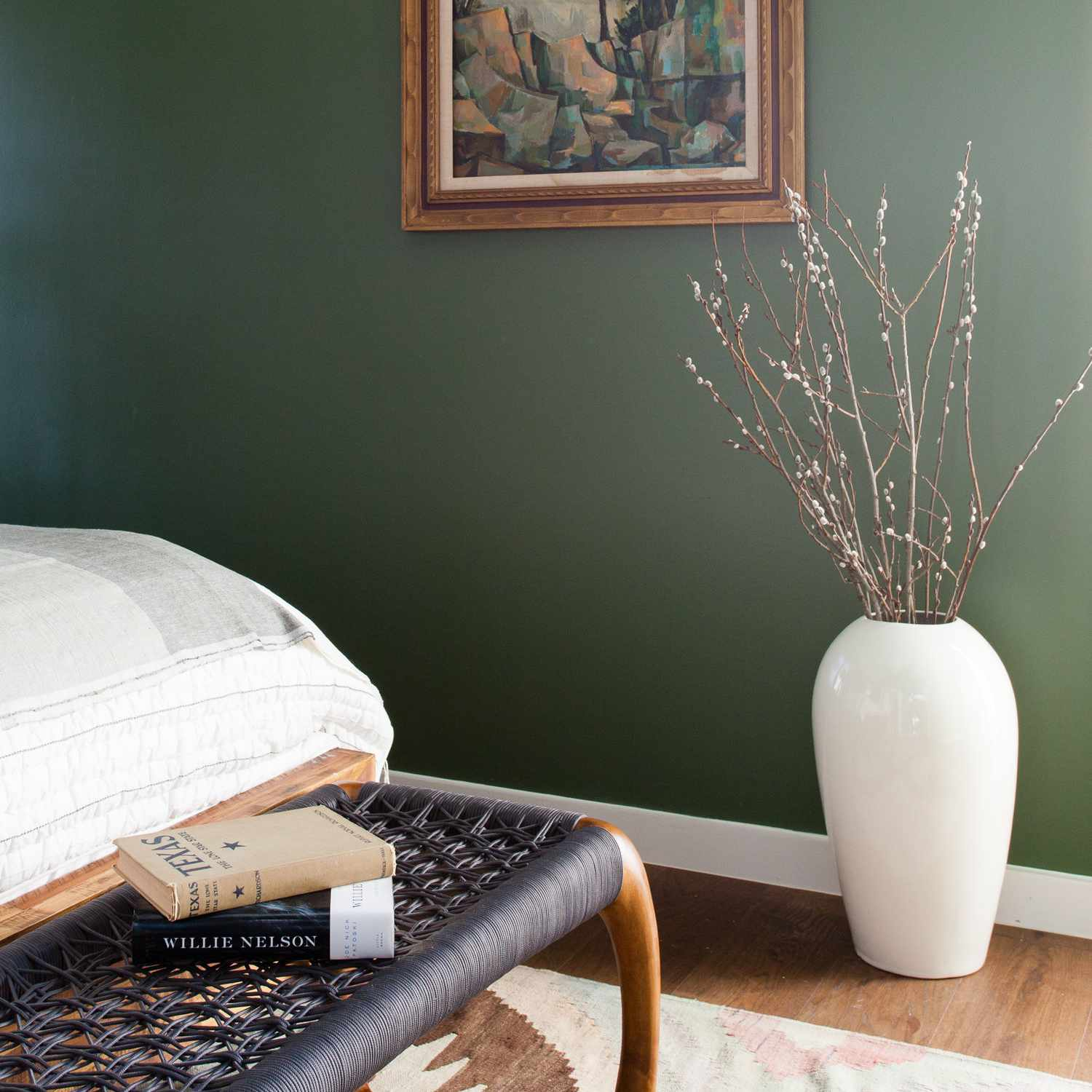 A green bedroom with a woven bench placed at the foot of the bed