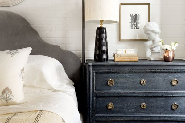 Blue nightstand with decorative objects.