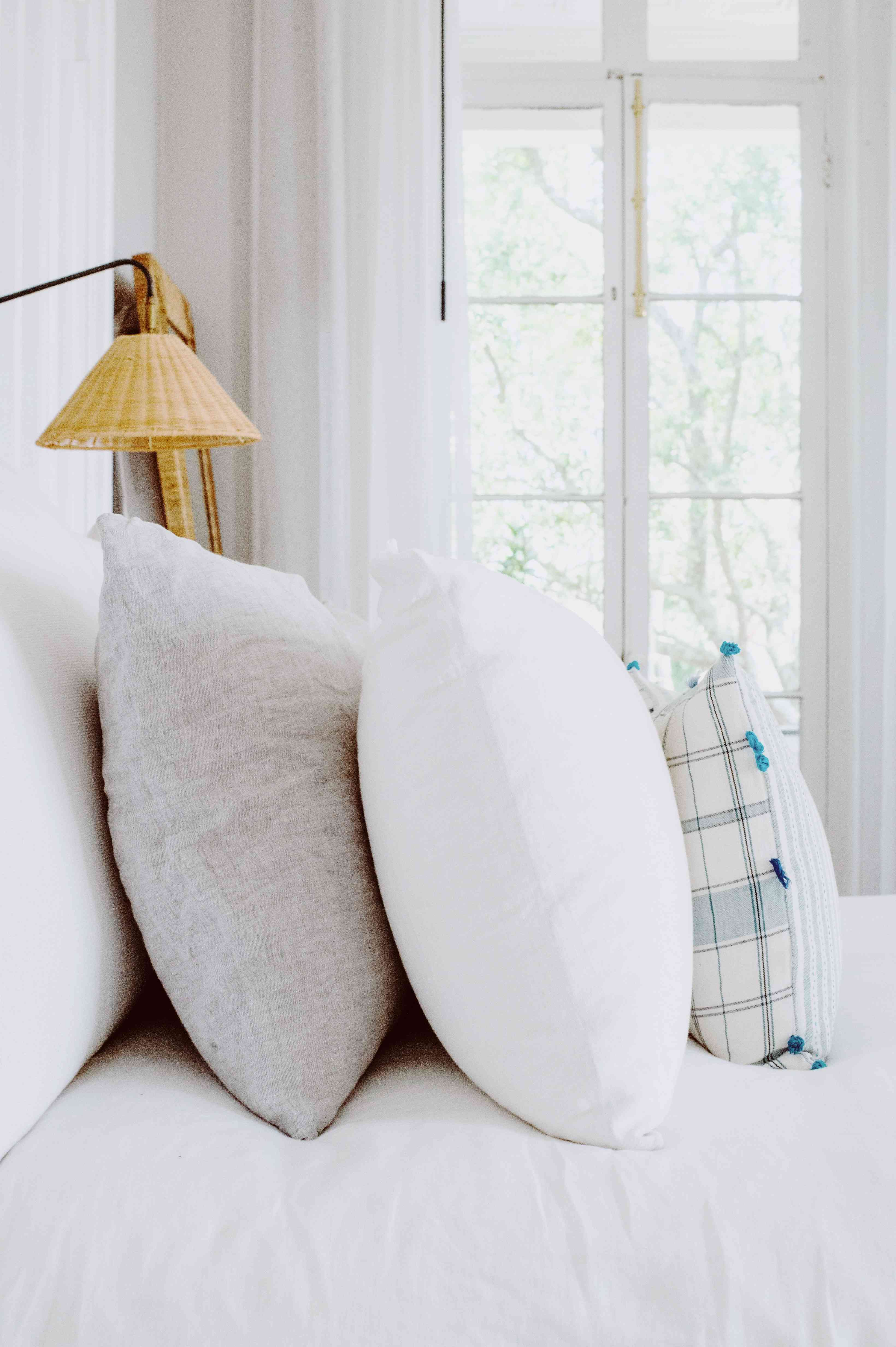 Amanda Greeley home tour - pillows stacked on bed in bedroom