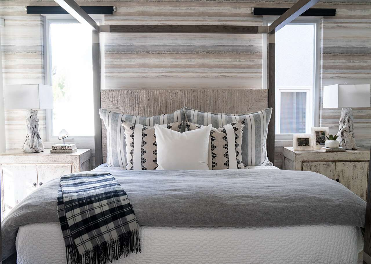 A bedroom with textured wallpaper, a textured canopy bed frame, and printed linens