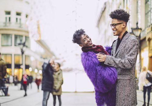 Joven pareja en abrigos bailan juntos afuera