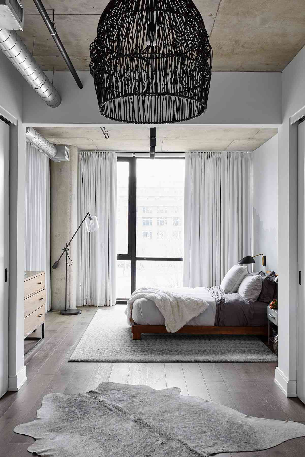 An industrial bedroom with curtains running from ceiling to floor