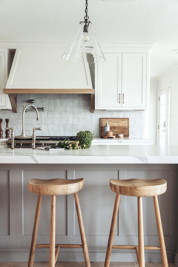 An all-white kitchen with square white backsplash tiles
