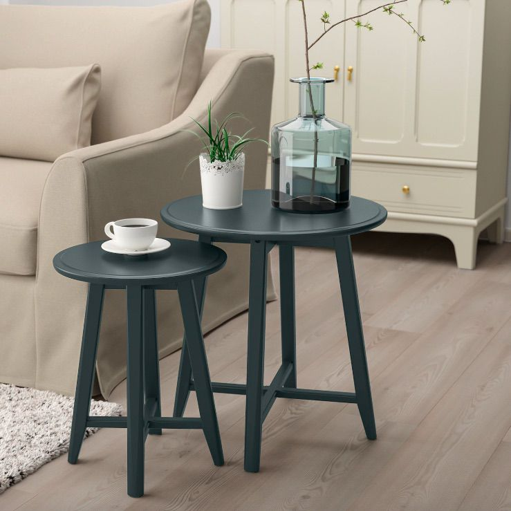 A set of two round blue nesting tables beside a sofa.