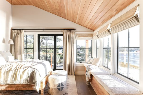 A light-filled bedroom with wood-paneled ceilings and floors
