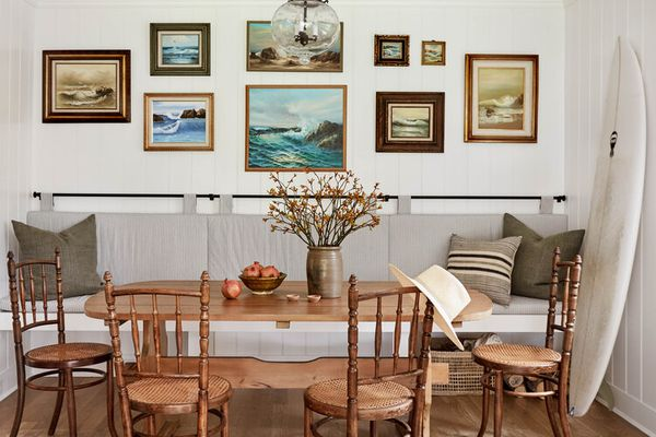 A kitchen table with a bench that's propped up against an art-lined wall