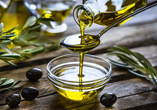Olive oil being drizzled into a cup on a wood table with herbs and olives.