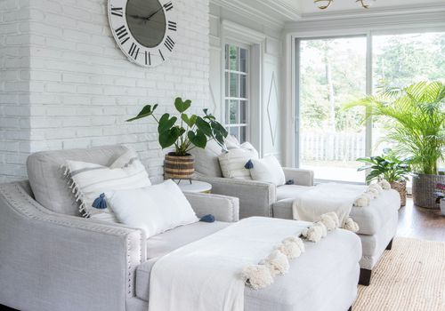 Sunroom with white brick wall, gray chaise lounges, and plants.